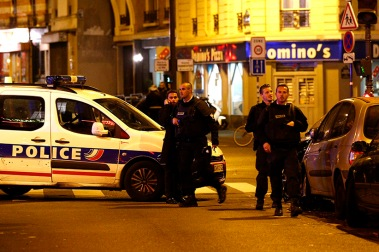 epa05023768 Police officers arrive at the scene of a shooting in Paris, France, 13 November 2015. A shooting occurred in a restaurant late 13 November in Paris, with newspaper Liberation reporting several dead. Explosions have also been reported near the Stade de France. (YOAN VALAT/EPA/CP)